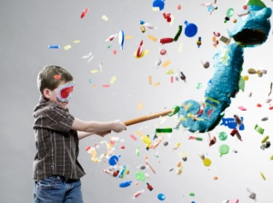 Boy hitting pinata, explosion of candy